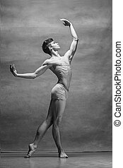 The male ballet dancer posing over gray background....