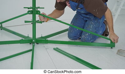The male engineer frames the construction basement of Cristmas tree with green pipes indoors.