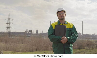 The male engineer projects the work. Sunny day and clouds. The man is dressed in a green sunglass vest