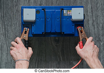 The male hand connects the terminals to the car's batteries on a wooden background