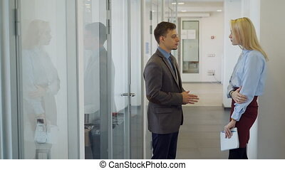 The male manager meets his new female colleague in the bright office corridor.