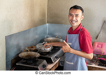 the male waiter smiles with a thumbs up while frying side ...