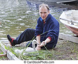 The man and a young swan at the lake ashore