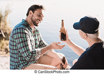 The man and the old man are sitting on the river bank and drinking beer against the background of the river.