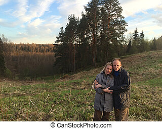 man and the woman in country clothes on a background of early spring Pine hill
