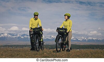 The man and woman travel on mixed terrain cycle touring with bikepacking. The two people journey with bicycle bags. Mountain snow capped.