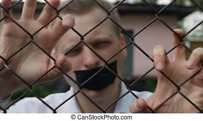 The man behind the bars with his mouth taped and shouting with his hands on the grille, close-up, slow-mo, disclosure of information
