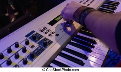 The man behind the synthesizer plays the keys. A rock band performs at a nightclub party.