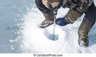 The man bore the ice ice screws. - The man bore the ice...