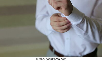 The man buttoning buttons on the sleeves of his shirt standing near the window.