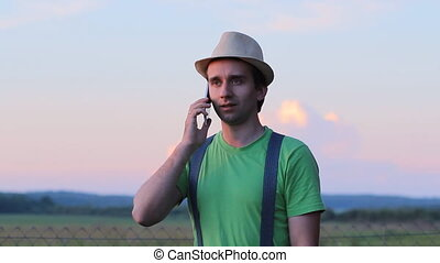 The man calls by phone. Against the backdrop of a beautiful sunset sky
