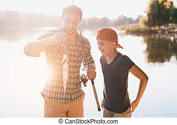 The man caught a big fish and shows it to his son. They stand on the background of the river