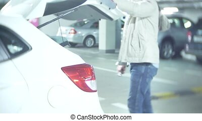 the man closes the trunk of the car in a covered parking lot and puts the car on a alarm. 4k
