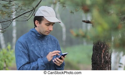 The man compose sms on the phone near a tree in the forest....