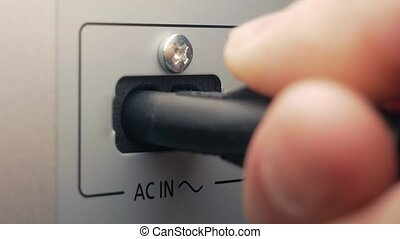 The man connects AC cable. AC input