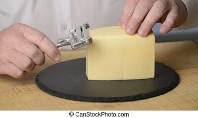 The man cuts cheese into thin slices with use of a cheese slicer on a black round chopping board from slate