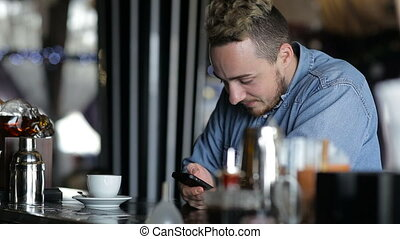 The man dials sms sitting at the bar