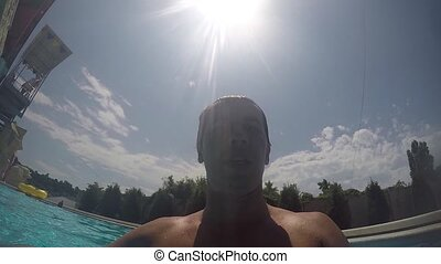 The man dives lifestyle swimming under the water. Happy man swims underwater in swimming pool