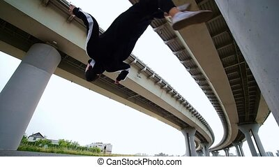 The man does flip back under the bridge, slow motion