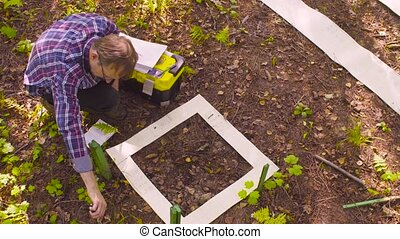 The man ecologist describes the plants inside the square...