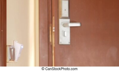 The man enters the hotel room and turns on the electricity by putting the key card in the device