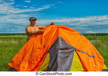 The man establishes a tourist tent. Summer day on the bank of the lake. Primitive nature.