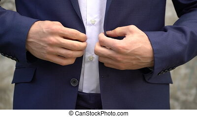 The man fastens buttons on his jacket close up.