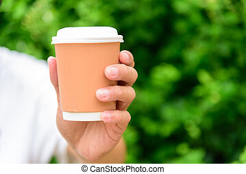 The man hand show a cup of hot coffee