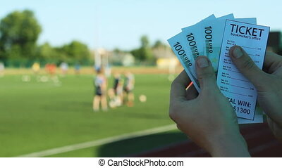 The man holds a winnings from the bookmaker office, in the hands of the euro money in the background of the stadium where players play football, close-ups, sports betting