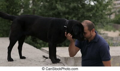 The man hugged the dog - The man hugged his dog in black