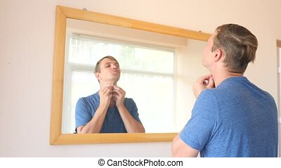 the man in front of the mirror squeezing out pimples. 4k slow motion. copy space
