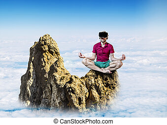 The man in glasses virtual reality sitting in the Lotus position on a rock