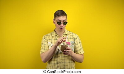 The man in sunglasses and a Hawaiian shirt is hot and drinking coconut pina colada. Shooting in the studio on a yellow background. 4k