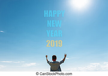 The man in the background, the blue sky, stretches his arms toward the sky. Text Happy New Year, on clouds, christmas concept.