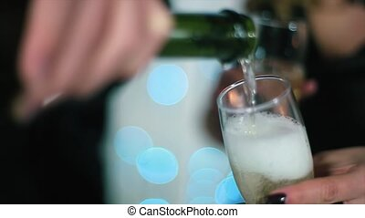 The Man in The Black Suit Pours Champagne, The woman in black evening dress holding a glass