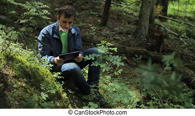 The man in the forest play on tablet in game. It sits on a small cliff green