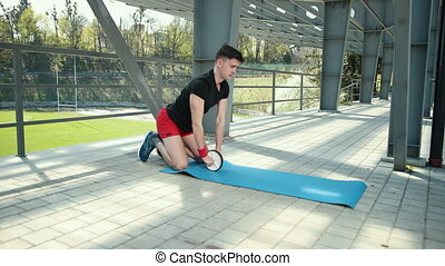 The Man In The Gym Is Engaged On A Wheel For The Press. Close-Up. The Wheel Bumps And Pulls Away From The Camera. The Guy Trains Near The Metal Pillars In The Background Of The Stadium. Dressed In A Black T-Shirt And Red Shorts. Prores, Slow Motion, 4k