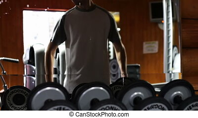The man in the gym shakes his biceps using weights.