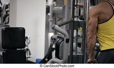 The man in the gym trains muscles of hands with a block circuit simulator