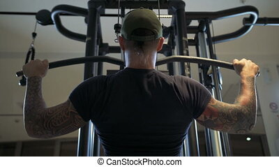 man in the gym trains the latissimus dorsi by the lat...