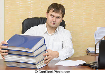 The man in the office at the table scans folders with documents