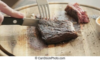 the man in the restaurant with a knife cuts steak of marble beef, grilled. Serving on a wooden Board. Beefsteak cooking on a kitchen. Fresh, delicious, spicy, juicy meat
