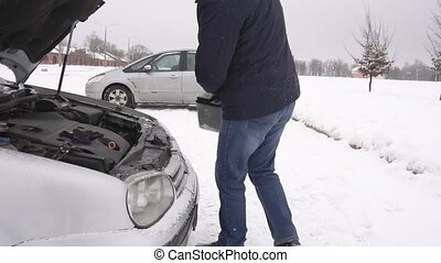 The man installs the battery in the car in the winter, the...