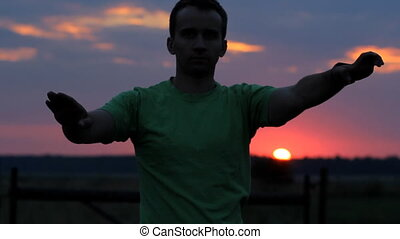 The man is dancing: does wave his arms on the background of a beautiful sunset.