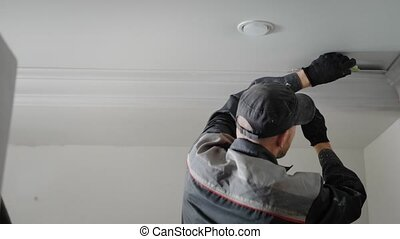 the man is doing repairs in the apartment, the person is...