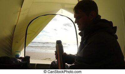 the man is drinking hot tea from a thermo mug against the backdrop of the view from the tent on the sea. Camping on the beach by the sea. 4k, slow motion