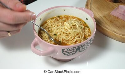 The man is eating Chinese instant noodles with a fork 4k