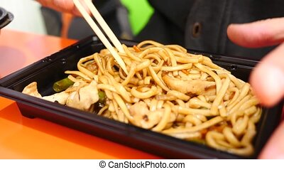 the man is eating Chinese noodles with chopsticks. 4k. Slow shooting.