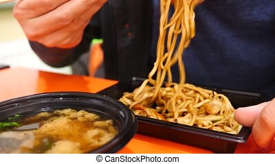 the man is eating Chinese noodles with chopsticks. 4k. Slow...