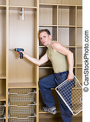 The man is engaged in repair and furniture assemblage